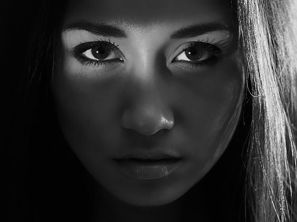 Portraitfoto einer jungen Frau in dunkler Umgebung mit einem hellen Lichtstreifen auf den Augen für Portraitfotos im Fotostudio