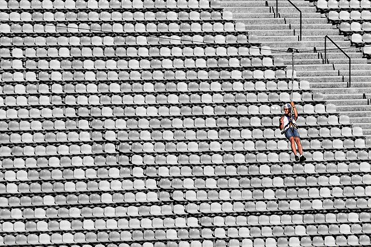 Eine Frau gleitet an einem Seil in luftiger Höhe durch das Münchner Olympiastadion